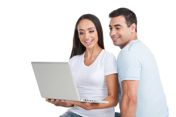 Indian loving  couple looking at white laptop.