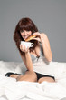 Smiling brunette woman is drinking coffee in the bed