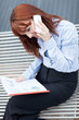 Red hair Businesswoman is sitting on a metal bench and phoning