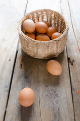 Eggs with basket on wooden floor
