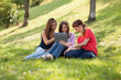 Three woman sitting on grass and looking at a digital tablet