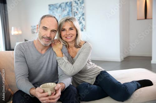 Leinwanddruck Bild Romantic senior couple relaxing in couch