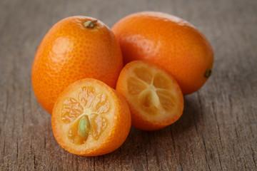 ripe kumquat fruits on wooden table