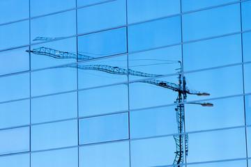 Grúa reflejada en edificio