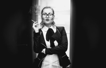 woman in glasses smoking cigarette outdoor against city view