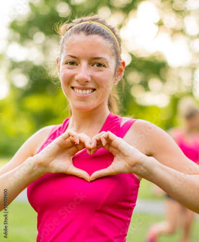 Young woman making a heart gesture