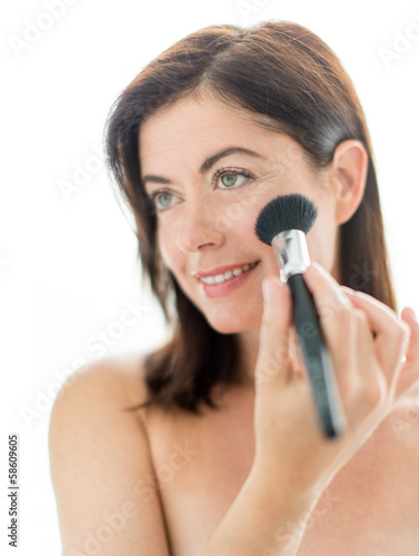 attractive woman applying makeup to her face