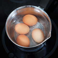 top view of boiling chicken eggs in metal pot