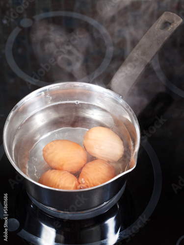simmering chicken eggs in metal pot
