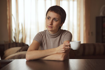 Thoughtful girl sitting with a cup of coffee