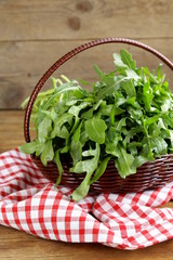 large bunch of arugula green salad on a wooden table