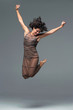 Attractive girl in brown dress jumps
