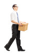 Smiling young man walking with a paper box in his hands
