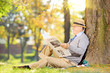 Senior reading a newspaper in a park at autumn