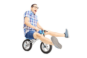 Nerdy young male riding a small bicycle