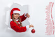 Little girl in santa costume leaning out of torn edges hole in p