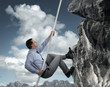 Businessman climbing mountain