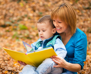 Mother is reading from tablet with her son