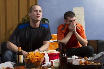Two sports fans anxiously watching game on TV
