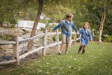 Happy Young Brother and Sister Running Outside