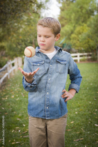 Handsome Young Boy Tossing Up Baseball in the Park
