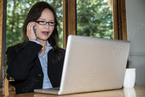 Woman with laptop and coffee on phone
