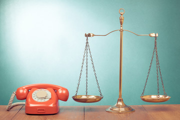 Law scales and retro red telephone on table