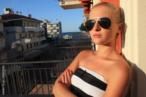 Stylish beautiful blond woman in Italy.on the balcony.sunglasses