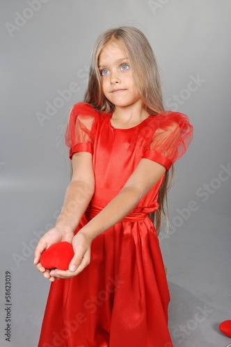 Valentine's Day. The girl in a red dress holding a heart
