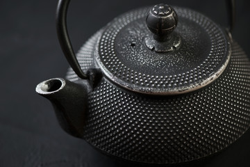 Horizontal shot of black asian cast-iron teapot, close-up