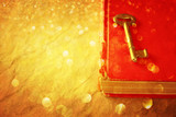 red book and vintage key and golden glitter lights