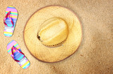 top view of straw hat and flip flops on beach sand