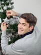 Happy Man Decorating Christmas Tree