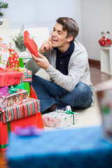Man Looking At Christmas Gift In House