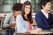 Student Sitting At Desk With Classmates In Classroom
