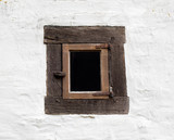 Old window on white wall of house