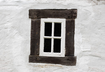 Old window on a white wall of house