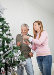 Happy Father And Daughter Decorating Christmas Tree