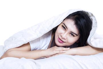 Beautiful woman under blanket in bed