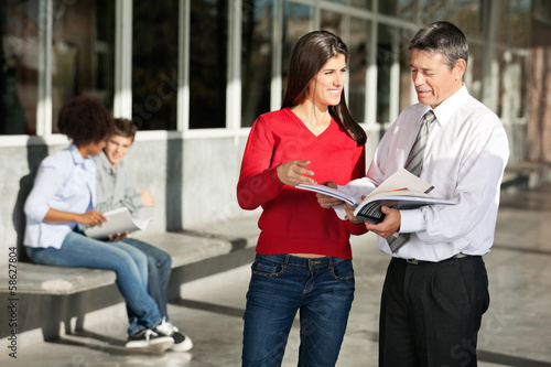 Female Student And Teacher Discussing Over Book On Campus