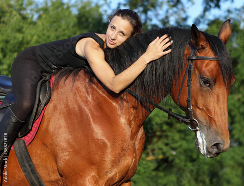 Young attractive equestrian woman hugging a horse