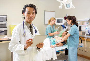 Doctor Holding Digital Tablet While Nurses Treating Male Patient