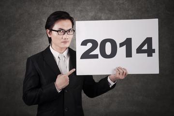 Businessman pointing a 2014 billboard