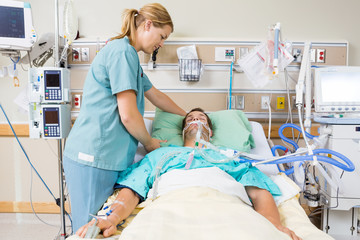 Nurse Adjusting Patient's Pillow