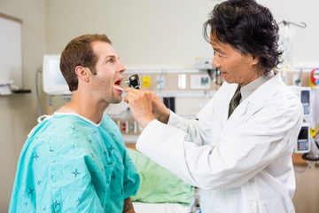 Doctor With Depressor And Otoscope Checking Patient's Mouth