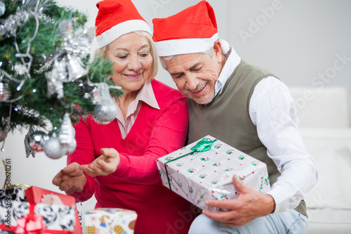 Senior Couple Looking At Present While Decorating Christmas Tree