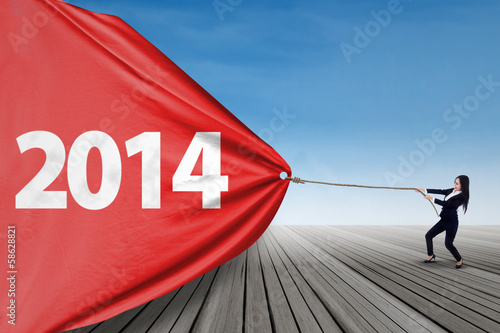 Businesswoman pulls banner of new year 2014