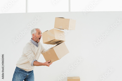 Side view of a mature man carrying boxes