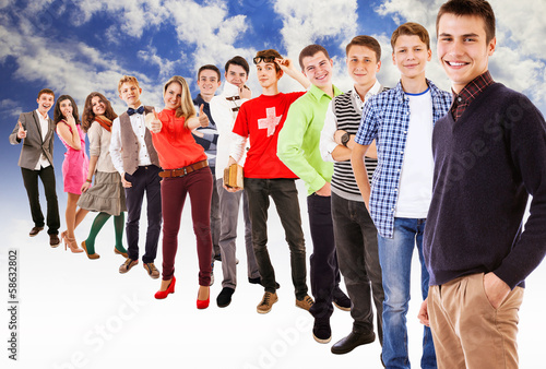 Large group of multicolored dressed teenagers on blue sky