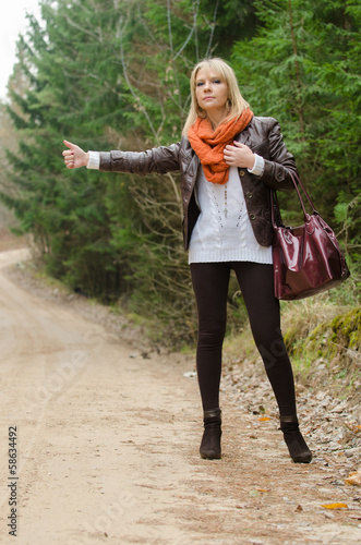 Pretty girl hitchhiking in the forest